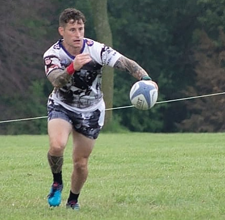 Rugby player runs towards a ball in mid-air.