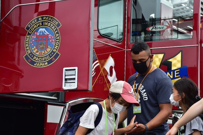 Lance Cpl. Joshua Dejesus, Combined Arms Training Center Camp Fuji motor transportation operator, helps local children explore the inside of a fire truck during a tour of Combined Arms Training Center Camp Fuji's fire department, Aug. 7, 2021, Shizuoka, Japan. Marines and Sailors from the installation volunteered with the camp and provided children the opportunity to speak with native English speakers. Dejesus is a native of Paterson, New Jersey. (U.S. Marine Corps photo by Katie Gray)