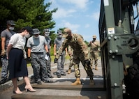 JASDF members watch as USAF members display different parts and actions of a forklift.
