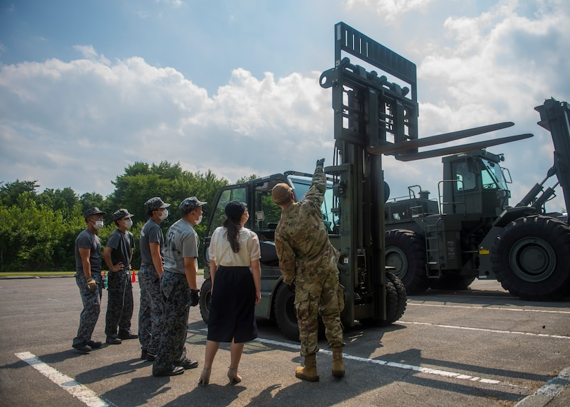 JASDF members watches as USAF members display different parts and actions of a forklift.