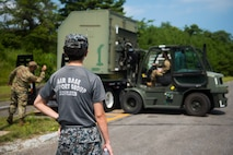 JASDF member watches as USAF members operate a forklift to place cargo on a truck.