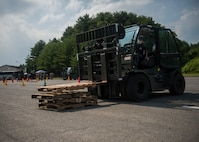 JASDF member operates a forklift to stack wooden pallets on the ground.
