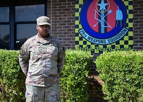 An Airman stands in front of a sign that displays the 29th Weapons Squadron patch.