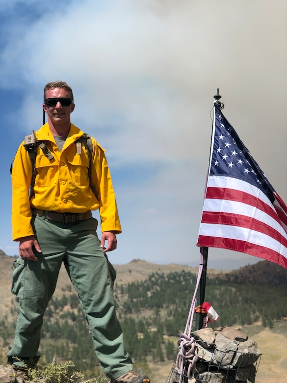 Members of the Pennsylvania Air National Guard are serving as imagery experts, providing live aerial video streaming to fire bosses working on the front lines of the devastating fires. Shown is Staff Sgt. William Gray, Pennsylvania National Guard posing with the American flag on an observation post in western Nevada on July 13.