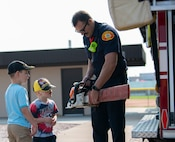 Firefighter show chainsaw to kids