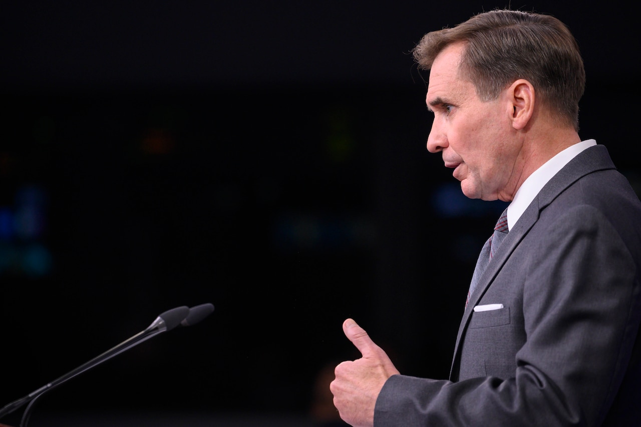 Pentagon Press Secretary John F. Kirby stands in front of a microphone.
