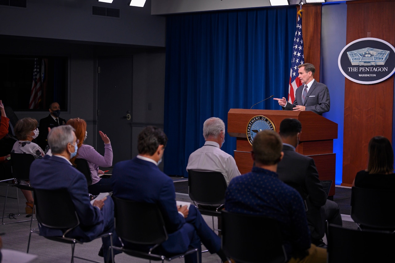 Pentagon Press Secretary John F. Kirby stands at a podium and speaks to a group of people.