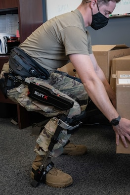 An Airman picks up a cardboard box while wearing a suit strapped to his hips, legs and feet.
