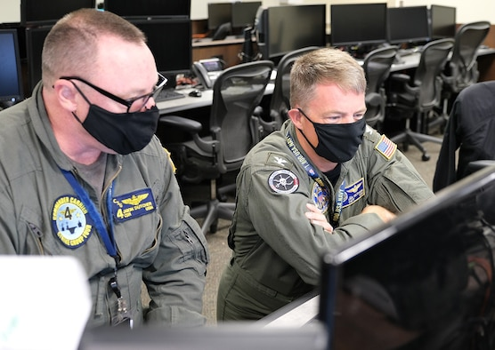 photo of two U.S. Navy members sitting looking at computer monitors.