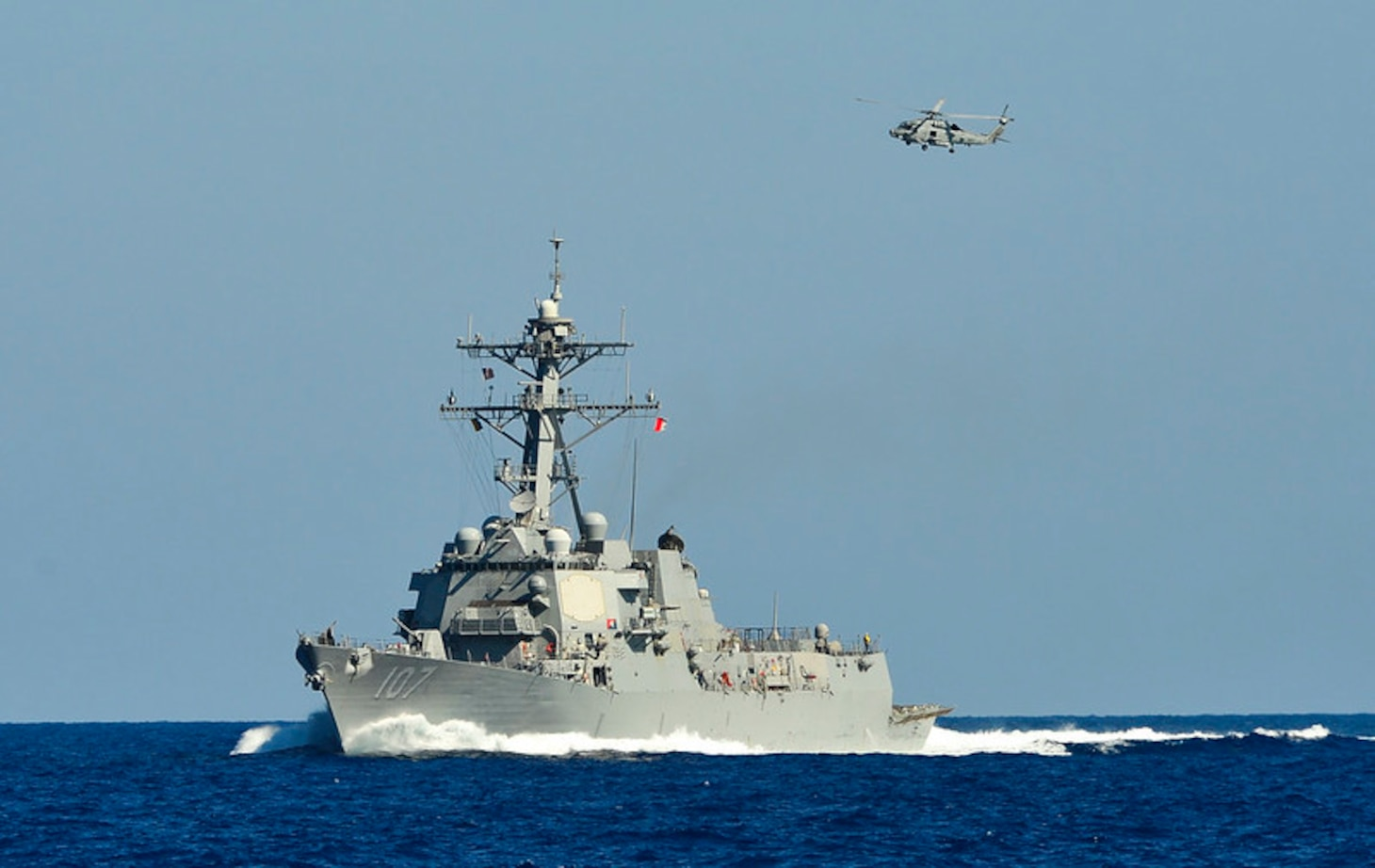 An MH-60R Sea Hawk helicopter from the Swamp Foxes of Helicopter Maritime Strike Squadron (HSM) 74 flies by the guided-missile destroyer USS Gravely (DDG 107). Gravely is deployed in support of maritime security operations and theater security cooperation efforts in the U.S. 6th Fleet area of operations.