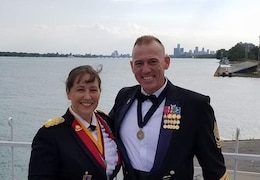 Two Soldiers stand next to each other smiling in their dress mess uniforms with a lake behind them.