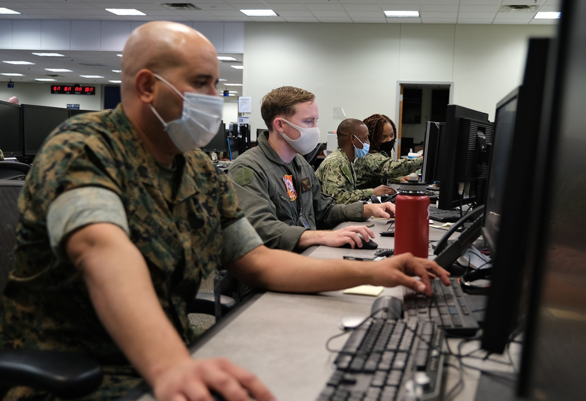 Photo of U.S. Service men and women sitting at computers