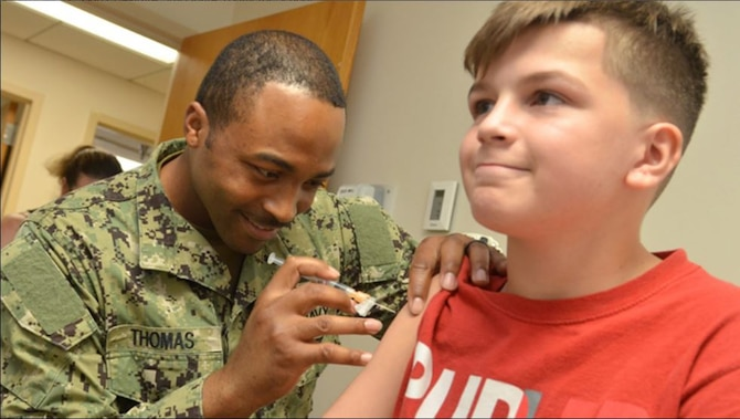 Naval Hospital Corpsman 2nd Class Vernon Thomas, a preventive medicine technician, gives a vaccine to a military family member at Naval Hospital Jacksonville's Immunizations Clinic, Aug. 8, 2019. (U.S. Navy photo by Petty Officer 1st Class Jacob Sippel)