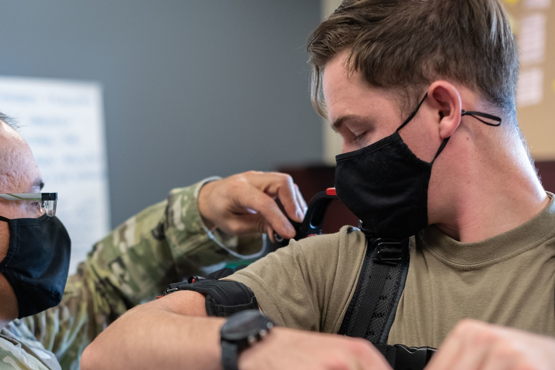An Airman looks on as another Airman straps a suite to his shoulder and arms.