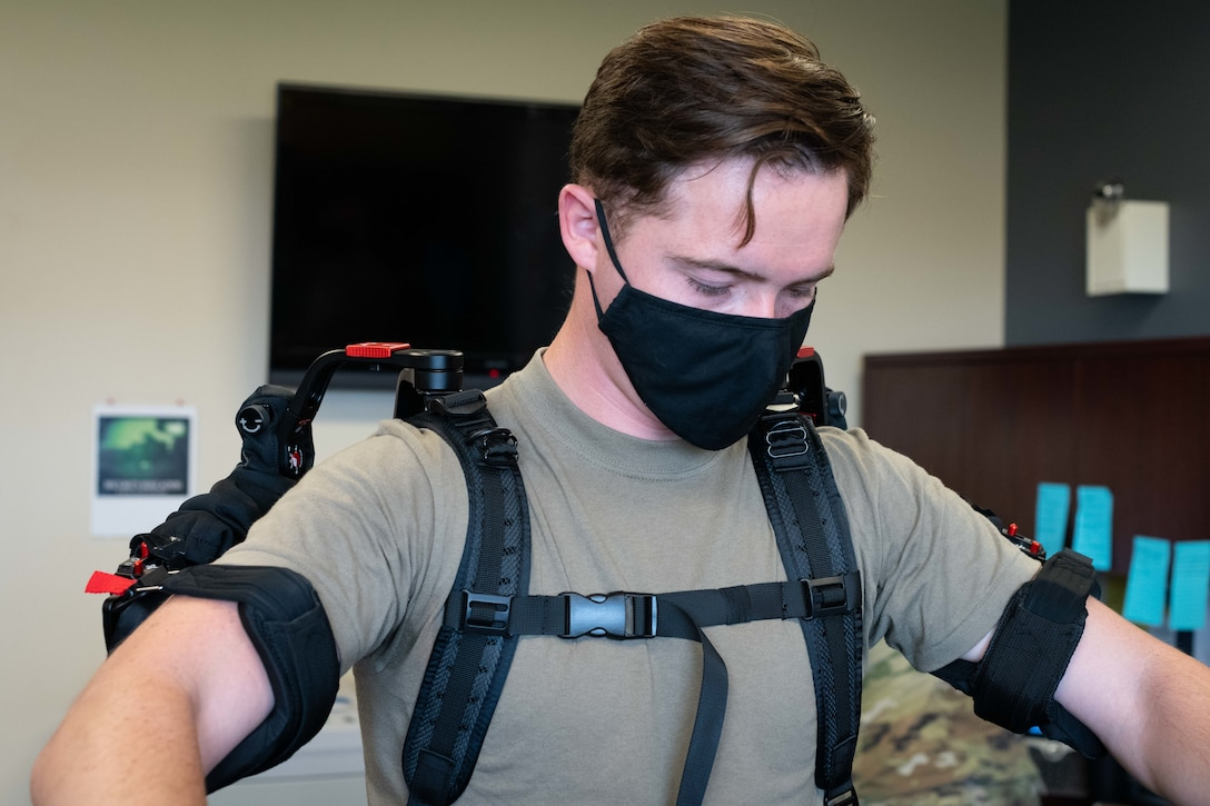 Airman stands with suit strapped around shoulders and arms.
