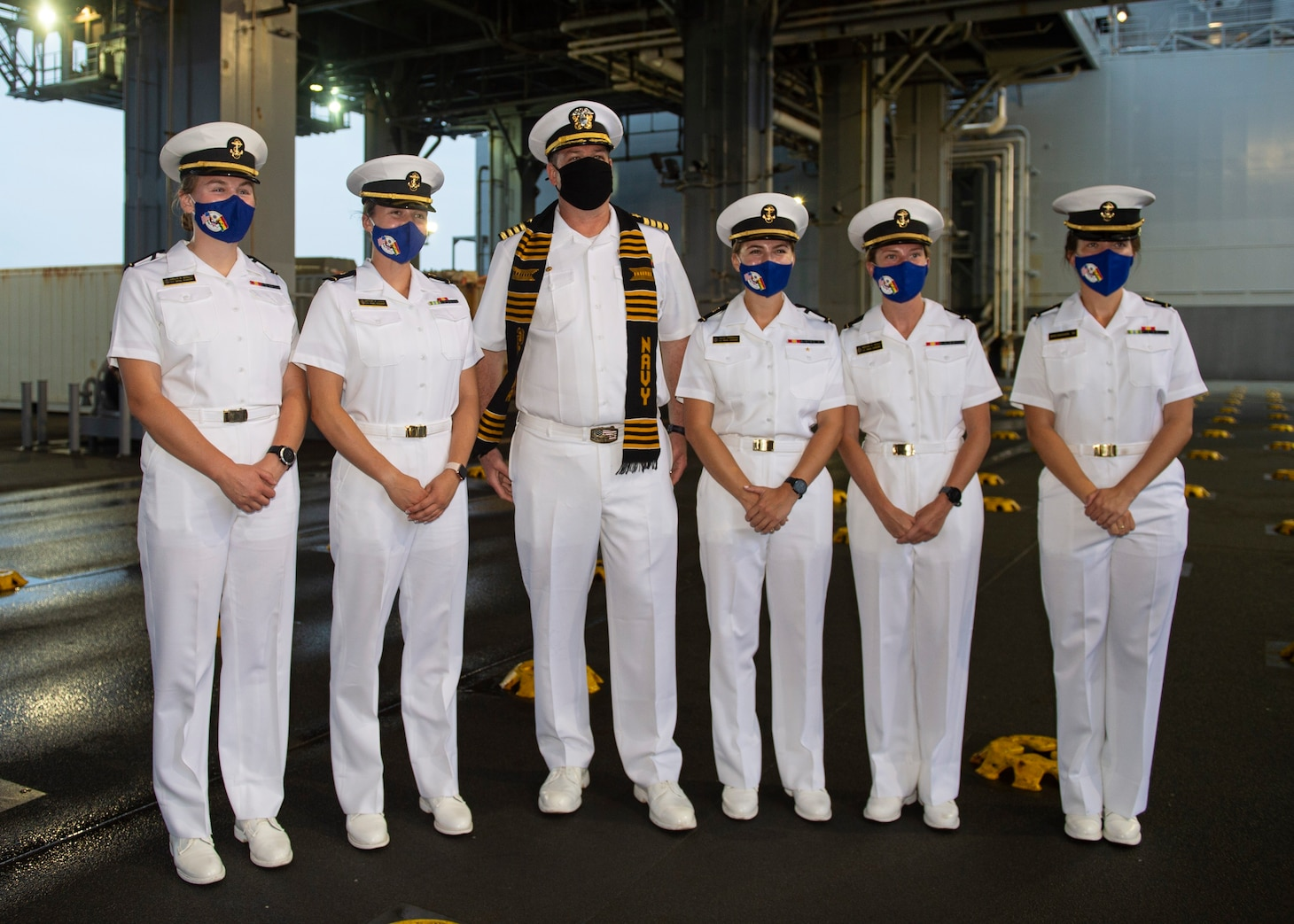 """Capt. Chad Graham, commanding officer of the Expeditionary Sea Base Hershel """"Woody"""" Williams (ESB 4), third from left, poses with midshipmen from the United States Naval Academy following a tour of the ship, Aug. 13, 2021."""