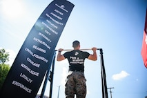 U.S. Marine Staff Sgt. Jorden MacIntyre, a recruiter with Recruiting Station Cleveland, executes a pull-up as a demonstration at the Cuyahoga County Fair, at Middleburg Heights, Ohio, Aug. 14, 2021. The purpose of the event was for recruiters to engage with the local community and to invite civilians to participate in a pull-up challenge to earn Marine Corps Prizes. (U.S. Marine Corps photo by Cpl. Nello Miele)
