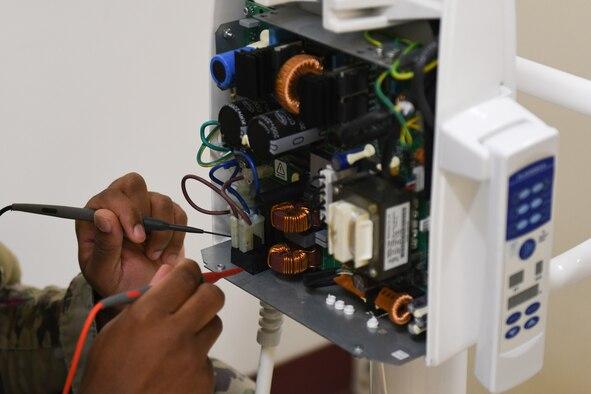 A Biomedical Equipment Technician program student troubleshoots medical equipment at the Medical Education and Training Campus.