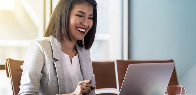 Lady smiling while looking at her computer.