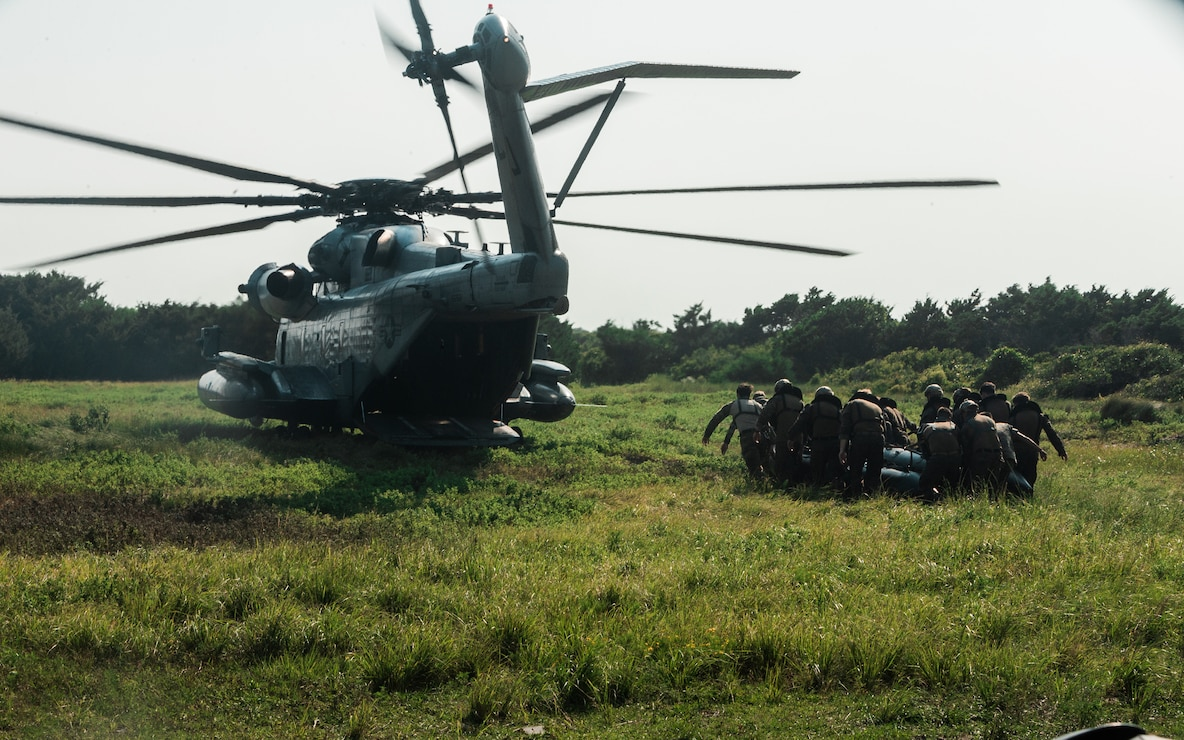 U.S. Marines with 3d Platoon, Force Company, 2d Reconnaissance Battalion, 2d Marine Division, prepare to board a CH-53E Super Stallion during an amphibious training event on Camp Lejeune, N.C.,  Aug. 11, 2021. The training event involved joint participation and cooperation with 2d Marine Aircraft Wing and U.S. Army Ranger Reconnaissance Team 4, 75th Ranger Regiment, to refine amphibious capabilities, confidence, and proficiency. (U.S. Marine Corps photo by Cpl. Patrick King)