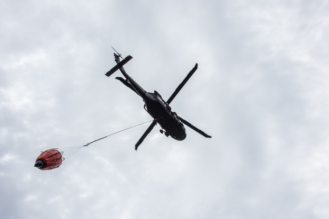 A bucket swings in the air as it hangs from a helicopter.