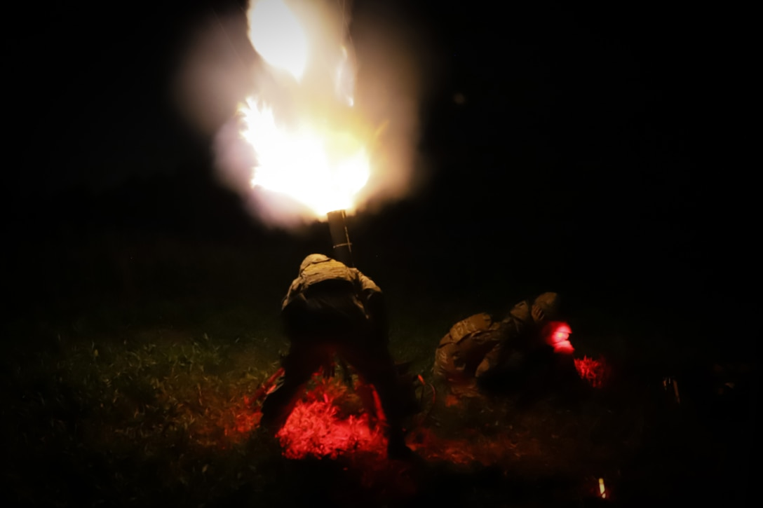 Soldiers fire a large weapon at night lighting up the darkness.