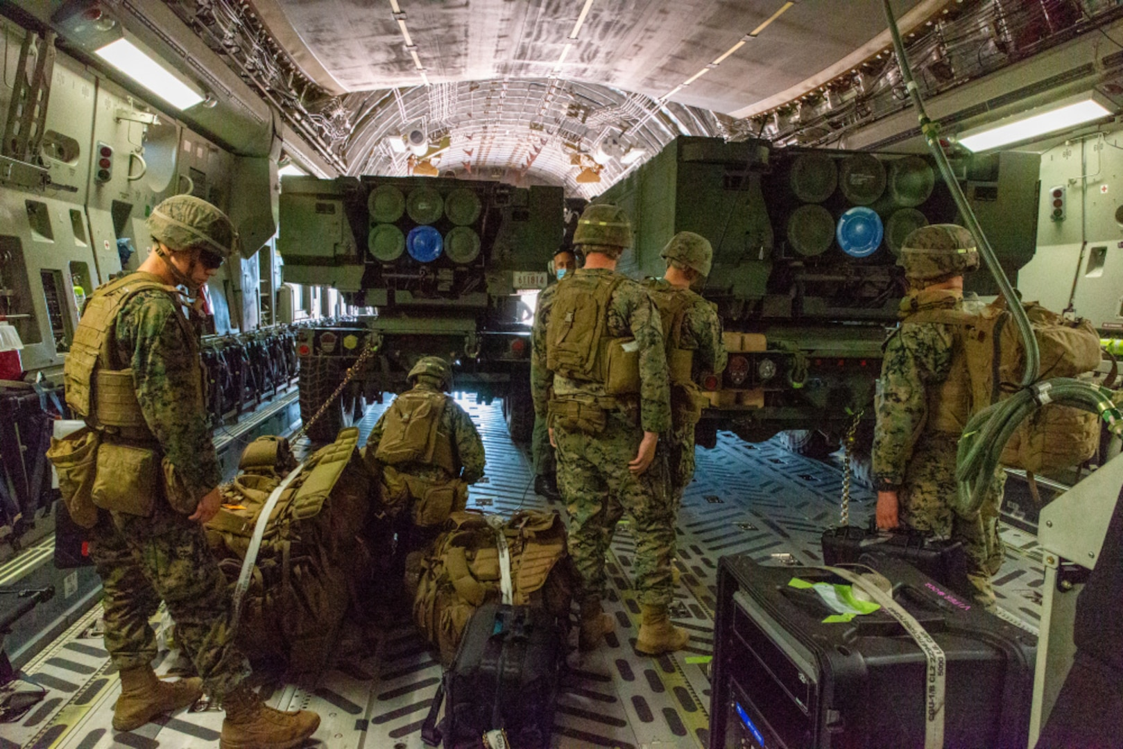 HIMARS unload from a C-17 to conduct HIRAIN during Exercise Loobye
