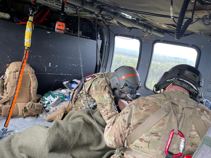 Staff Sergeant Damion Minchaca (left), an Alaska Army National Guard flight paramedic, provides critical en route care to a 75-year old man after he fell into a river and drowned, requiring immediate resuscitation, and sustaining multiple injuries, Aug. 12, 2021. Spec. Stefano James (right), a UH-60L Black Hawk medevac helicopter crew chief, provided medical assistance. The aircraft and crew, from Detachment 2, G Company, 2nd Battalion, 211th Aviation Regiment, hoisted the patient into the aircraft and provided medevac support. A fishing guide saved the patient's life, and the seamless, joint effort of the Alaska Air National Guard's Rescue Coordination Center and Army National Guard's Det. 2, G-Co, 2-211th AVN ensured a successful rescue and crucial medical care during transport to Providence Alaska Medical Center in Anchorage. The patient was delivered to the hospital within two hours of the AST request for support, and he was passed directly to a physician on site for continuation of necessary medical care. (Courtesy photo by U.S. Army National Guard crew chief, Staff Sgt. Bradley McKenzie)