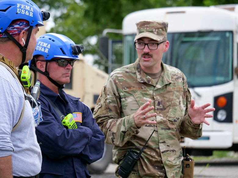 A member of the Indiana National Guard discusses mission plans with civilian counterparts during exercise Homeland Defender Aug. 14, 2021. More than 500 Soldiers, Airmen and civilian first responders participated in the scenario involving an earthquake and cyberattacks.
