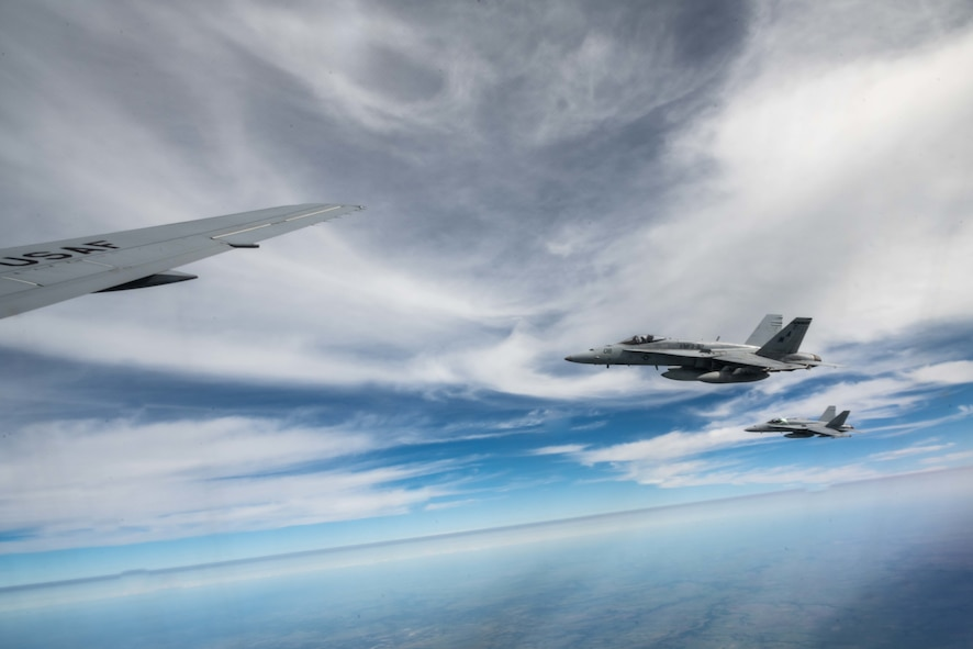 An F/A-18 Hornet from Marine Fighter Attack Squadron 112, Fort Worth, Texas, flies in formation with a KC-46A Pegasus from the 22nd Air Refueling Wing, McConnell Air Force Base, Kansas, while awaiting fuel Aug. 11, 2021.