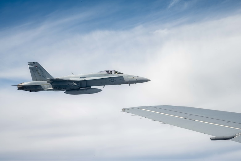 F/A-18 Hornets from Marine Fighter Attack Squadron 112, Fort Worth, Texas, fly in formation with a KC-46A Pegasus from the 22nd Air Refueling Wing, McConnell Air Force Base, Kansas, after being refueled by the aircraft Aug. 11, 2021.
