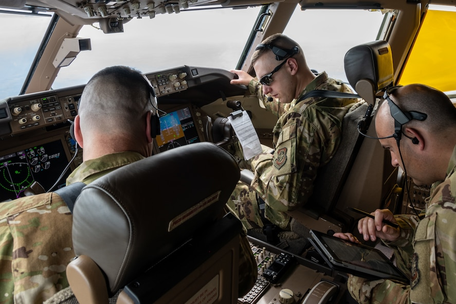 (From left) Lt. Col. Joshua Moores, 344th Air Refueling Squadron commander, 1st Lt. Brandon Sweet, 344th ARS KC-46A Pegasus pilot, and Senior Master Sgt. Lindsay Moon, 22nd Operations Group senior enlisted manager, review drogue procedures in preparation to refuel F/A-18 Hornets from Marine Fighter Attack Squadron 112, Fort Worth, Texas, Aug. 11, 2021.