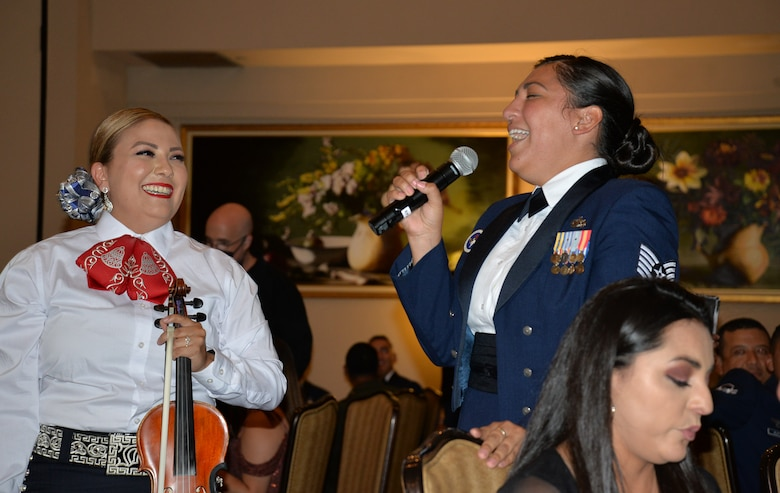 Tech Sgt. holds mike and sings while mariachi group member smiles.