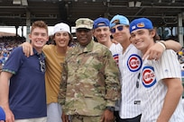 U.S. Army Reserve Command Sgt. Maj Theodore Dewitt, center, pauses for a photo with game spectators after receiving an honor for his service during the Chicago Cubs home game, at Wrigley Field in Chicago, August 12, 2021.