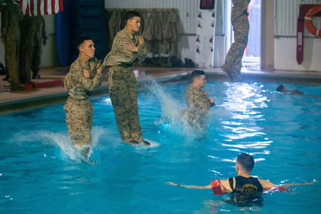 Three Marines jump into a pool with their uniforms on.
