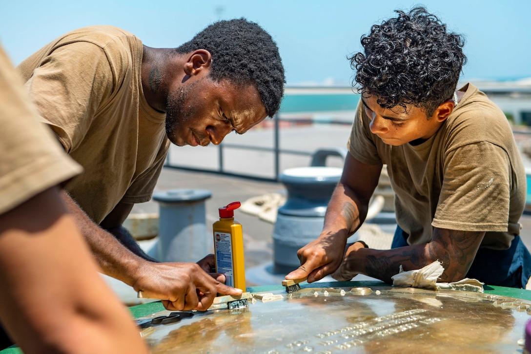 Two sailors polish a capstan aboard a ship.