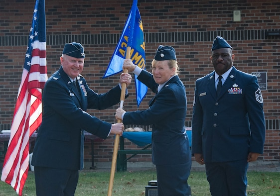 Col. Thomas Pemberton, 434th Air Refueling Wing commander, passes the guidon to Lt. Col. Kelli Bermudez, 434th Aerospace Medicine Squadron commander, during an assumption of command ceremony at Grissom Air Reserve Base, Ind., Aug. 8, 2021.