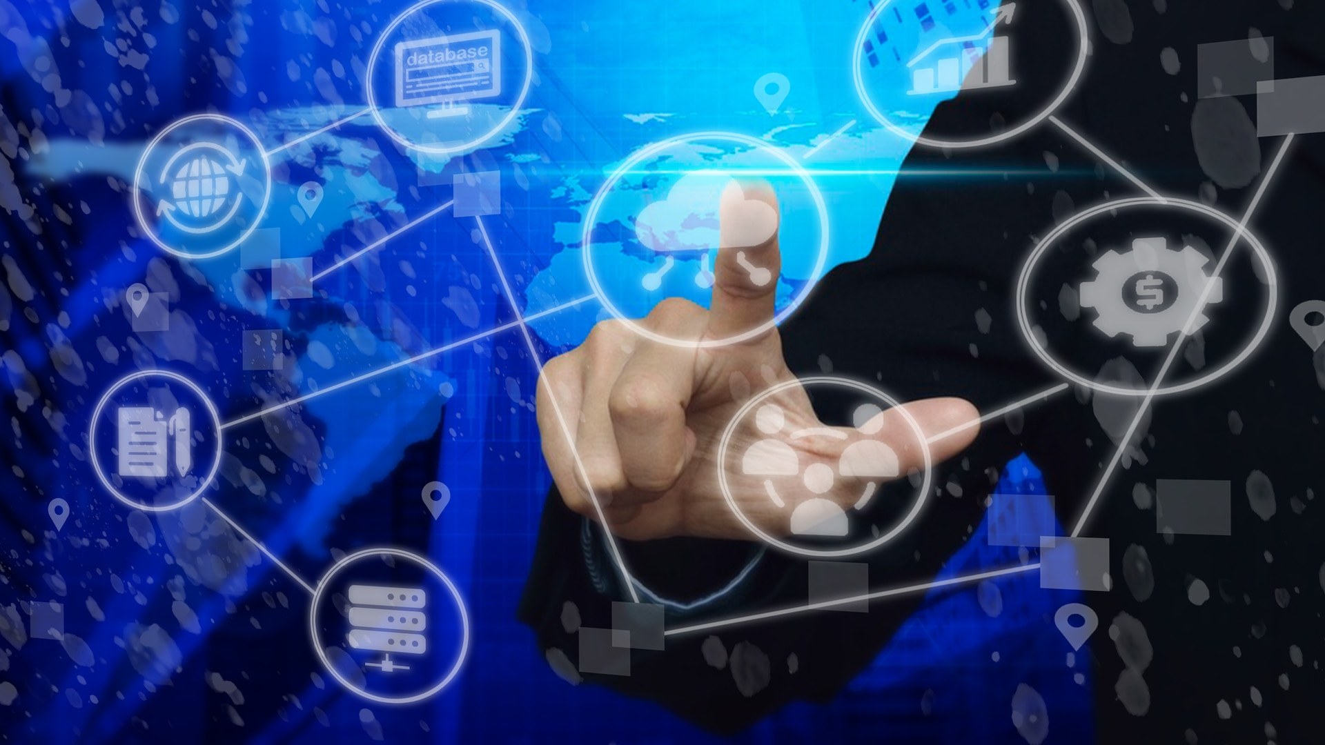 Graphic of a finger pointing at icons on a computer screen. Icons represent money, computer, world, etc.