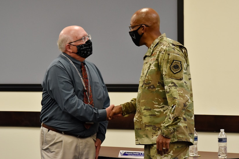 Russ Foos, Air Force Operational Test and Evaluation Center training chief, receives a coin of excellence from Air Force Chief of Staff Gen. CQ Brown, Jr., during CSAF's visit to the center at Kirtland Air Force Base, N.M., Aug. 12, 2021. Brown visited the course where both Air and Space Force students are taught how to plan, execute and report operational testing throughout the acquisition of combat capability.
