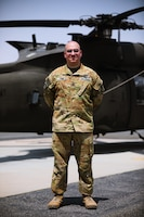1st Sgt. Matthew Gwin, maintenance noncommissioned officer in charge, 1100th Theater Aviation Support Maintenance Group, stands in front of a UH-60 Blackhawk helicopter at Camp Buehring, Kuwait, July 26, 2021. Gwin provided guidance to the 19 Soldiers from the 82nd Combat Aviation Brigade who deployed to Kuwait to augment the 1100th TASM-G and help alleviate a shortage of aviation contractors due to the COVID-19 pandemic. (U.S. Army photo by Sgt. Jimmie Baker)