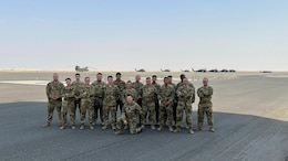 Soldiers assigned to the 82nd Combat Aviation Brigade stand on the flight line at Camp Buehring, Kuwait, July 26, 2021. The 19 Soldiers deployed to Kuwait to provide direct support to the 1100th Theater Aviation Support Maintenance Group and help alleviate a shortage of aviation contractors due to the COVID-19 pandemic. (Courtesy Photo)