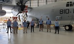 Seven personnel pose in front of an aircraft inside a hangar.