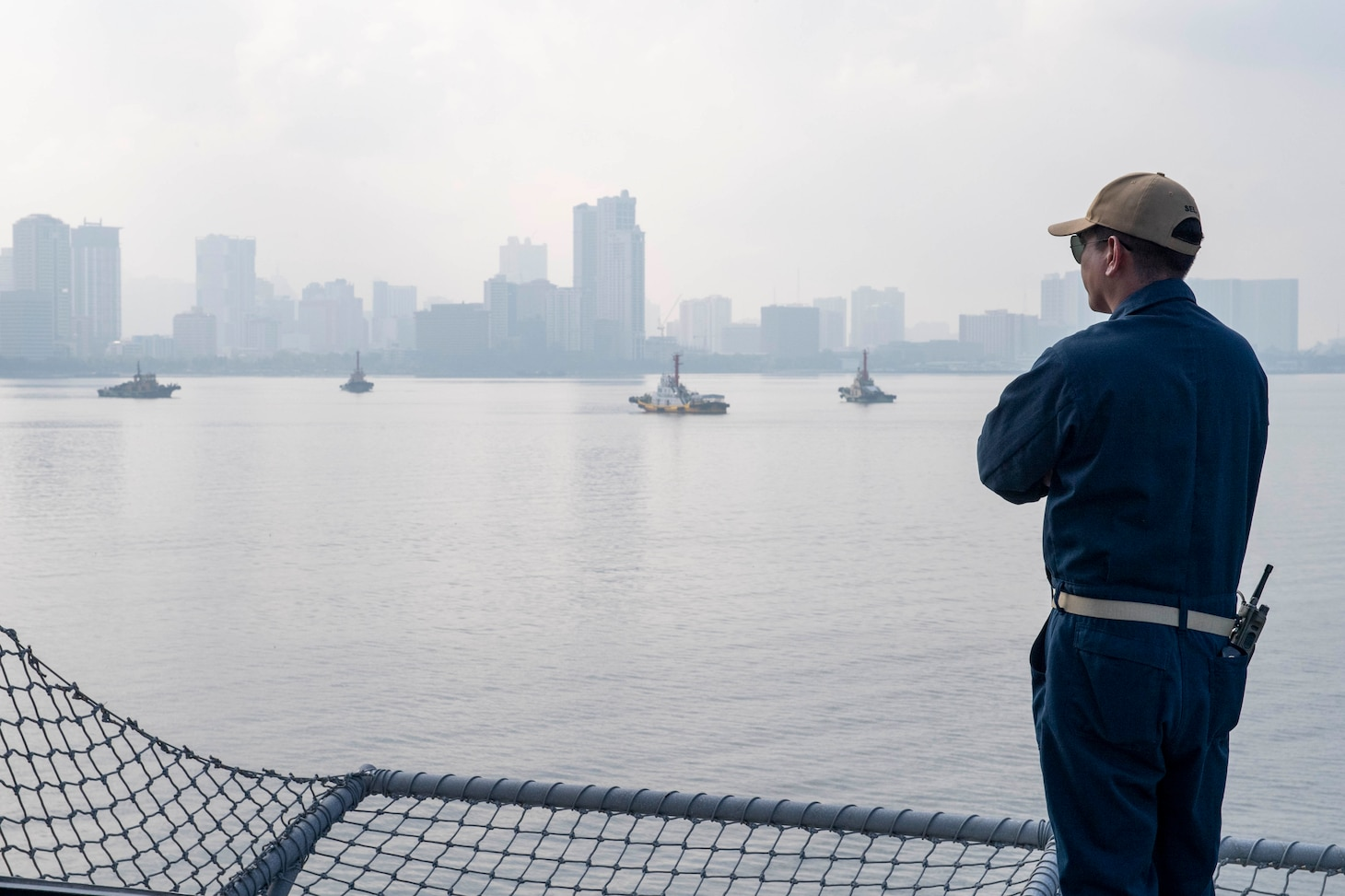 Command Senior Chief Donald Alvarado, from Tucson, Ariz., watches as Independence-variant littoral combat ship USS Charleston (LCS 18) pulls into port, Aug. 16. Charleston, part of Destroyer Squadron Seven, is on a rotational deployment operating in the U.S. 7th Fleet area of operation to enhance interoperability with partners and serve as a ready-response force in support of a free and open Indo-Pacific region.