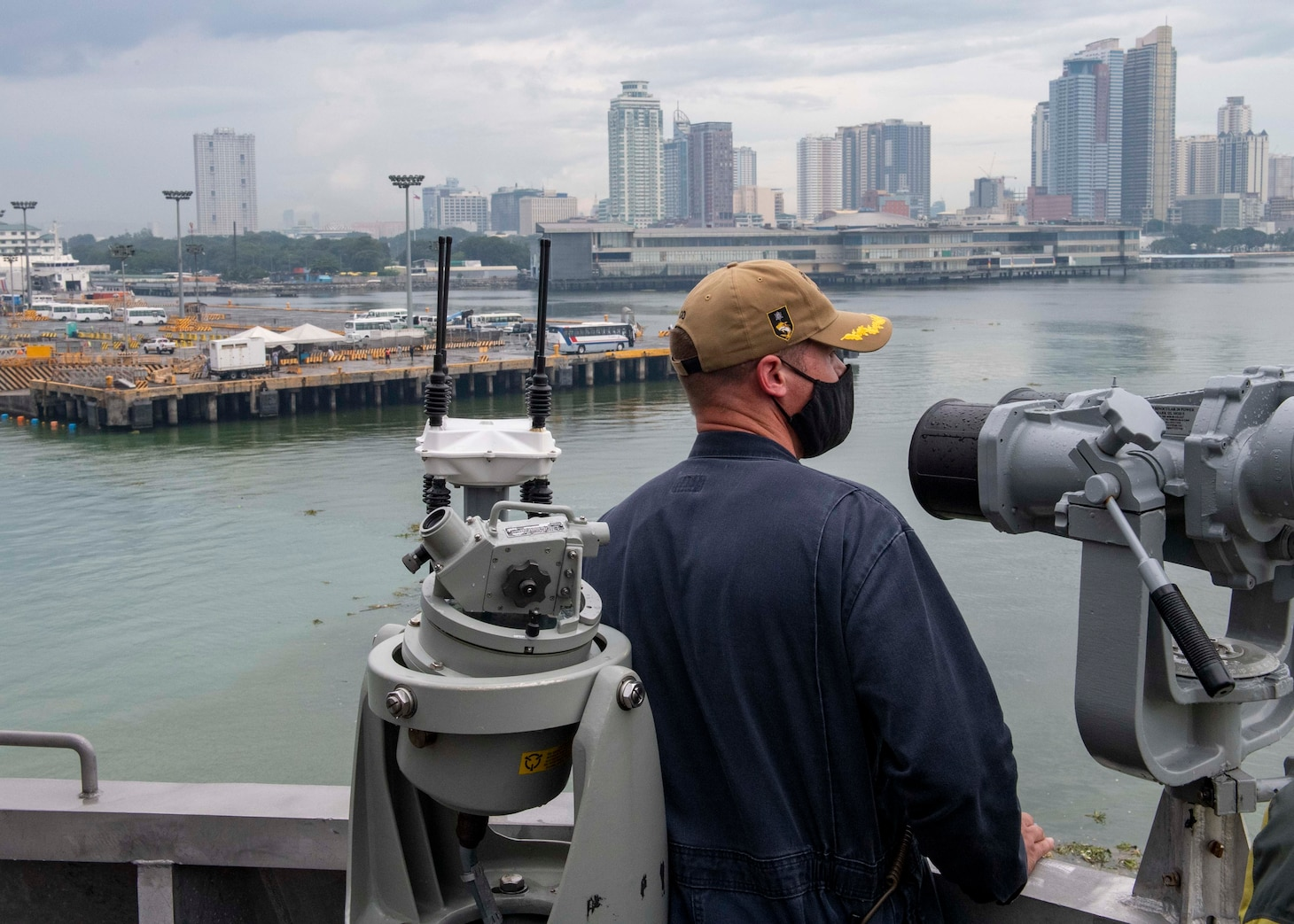 Cmdr. Joseph Burgon, commanding officer of Independence-variant littoral combat ship USS Charleston (LCS 18), looks at the city of Manila from the ship's bridge wing during a contactless port visit, Aug. 17. Charleston, part of Destroyer Squadron Seven, is on a rotational deployment operating in the U.S. 7th Fleet area of operation to enhance interoperability with partners and serve as a ready-response force in support of a free and open Indo-Pacific region.