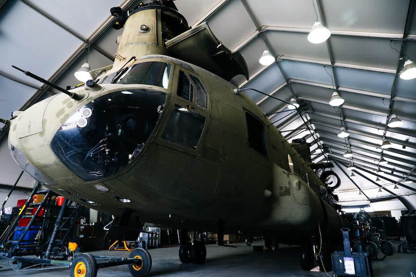 A CH-47 Chinook helicopter sits in a hanger awaiting phase maintenance at Camp Buehring, Kuwait, July 26, 2021. Phase maintenance can last anywhere between 25 and 45 days. Nineteen Soldiers assigned to the 82nd Combat Aviation Brigade deployed to Kuwait to provide direct support to the 1100th Theater Aviation Support Maintenance Group and help alleviate a shortage of aviation contractors due to the COVID-19 pandemic. (U.S. Army photo by Sgt. Jimmie Baker)