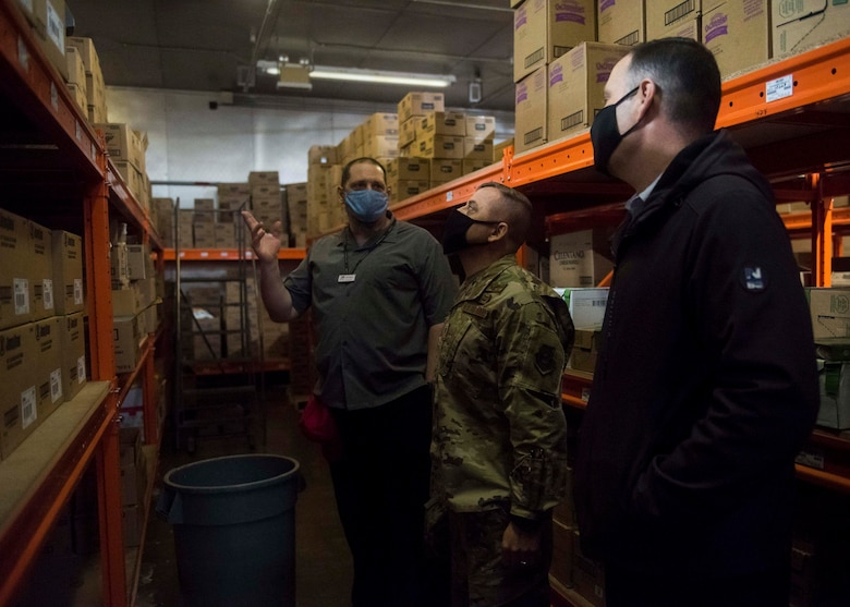 A commissary worker points something out to a military member