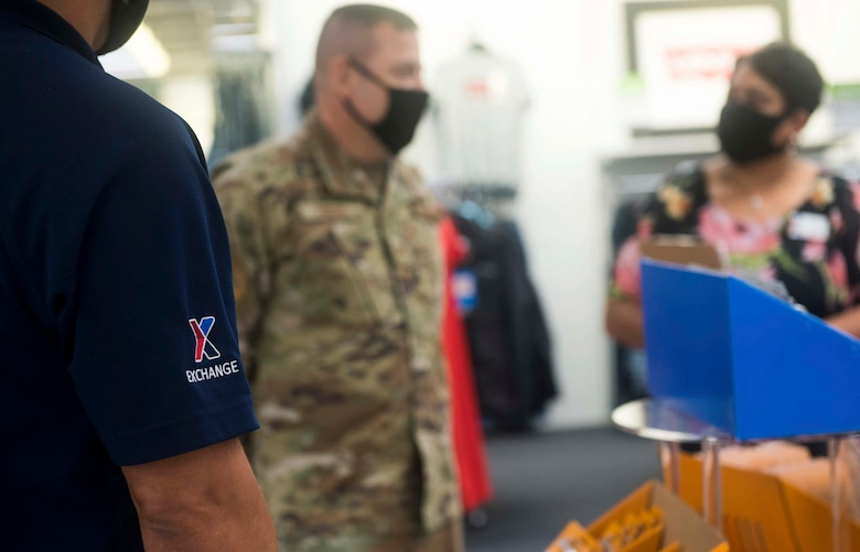 A military member listens to a BX worker at the BX.