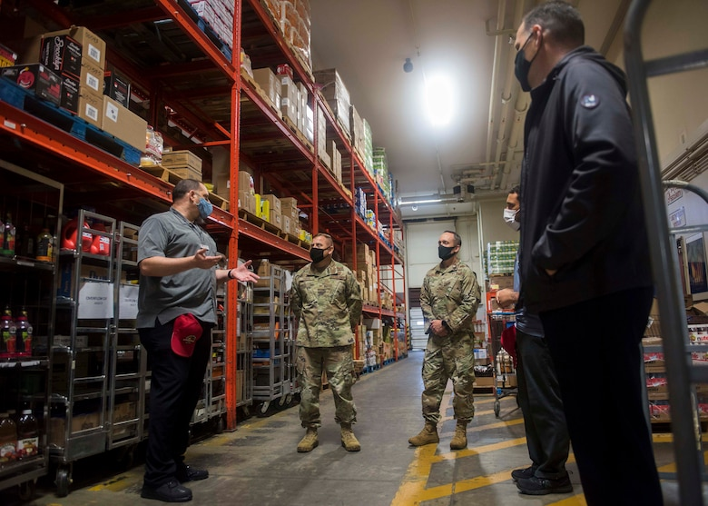 A commissary worker introduces the warehouse to two military members.
