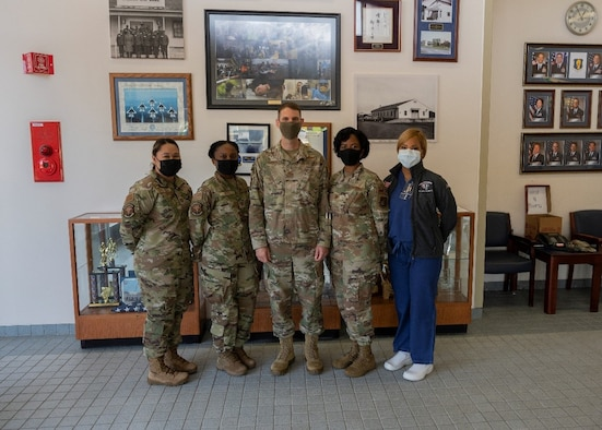 Five service members standing in a medical room talking.