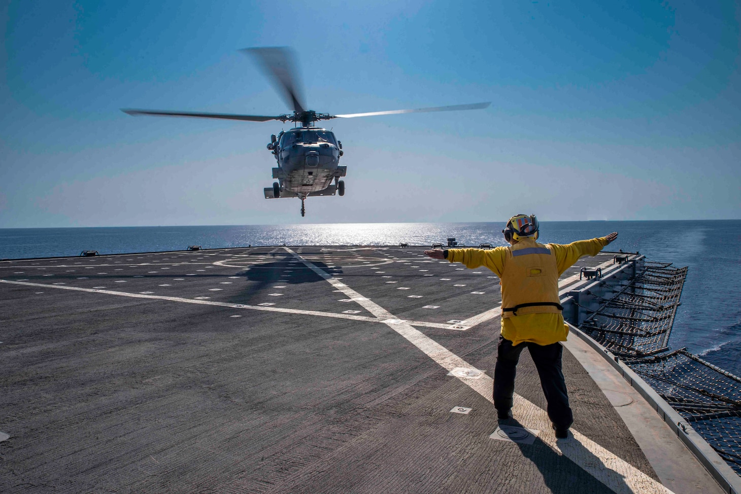 """A Military Sealift Command civil service mariner guides an MH-60 Sea Hawk helicopter attached to the """"Dragon Whales"""" of Helicopter Sea Combat Squadron (HSC) 28 to land aboard the Blue Ridge-class command and control ship USS Mount Whitney (LCC 20) while the ship conducts Large Scale Exercise 2021 in in Rota, Spain August 14, 2021."""